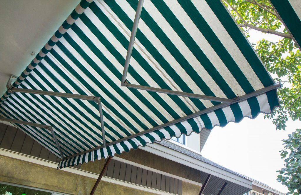 green and white striped awning with asphalt roof background